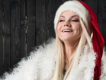 Mujer rubia encantadora en casquillo de la Navidad Fondo de madera oscuro Imágenes de archivo libres de regalías