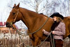 Mujer rubia encantadora en un caballo que hace una pausa del sombrero Fotografía de archivo