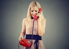 Mujer rubia enojada que recibe malas noticias en el teléfono fotos de archivo