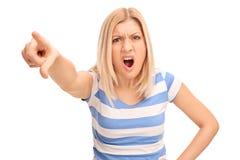 Mujer rubia enojada que regaña alguien imagen de archivo libre de regalías