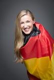 Mujer rubia envuelta en la bandera de Alemania Imagen de archivo