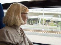 Mujer rubia feliz con los vidrios, miradas hacia fuera la ventana del tren, viaje, viaje Imagen de archivo