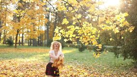 Mujer rubia feliz en top atractivo y la falda de la cosecha que juegan con follaje en parque almacen de metraje de vídeo