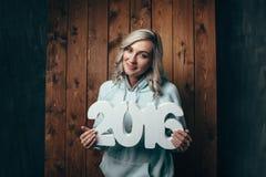 Mujer rubia feliz que lleva a cabo 2016 números Imágenes de archivo libres de regalías