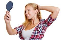 Mujer rubia feliz que mira en el espejo Fotos de archivo libres de regalías