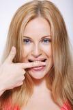 Mujer rubia feliz que muerde su finger. Aislado en blanco. Fotos de archivo