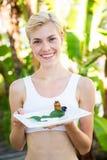Mujer rubia feliz que presenta la placa con la medicina herbaria Fotos de archivo