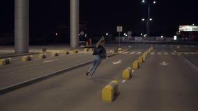 Mujer rubia feliz que se divierte al aire libre en la noche cerca del edificio del aeropuerto Corriendo, imitando el avión, salta almacen de metraje de vídeo