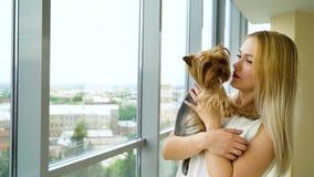Mujer rubia feliz que sostiene el pequeño perrito mullido en las manos y que lo besa almacen de video