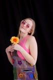 Mujer rubia feliz que sostiene la flor amarilla en equipo del hippy Aislado en fondo negro Imágenes de archivo libres de regalías