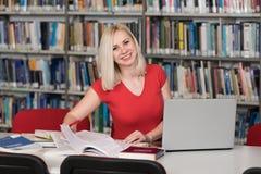 Mujer rubia feliz que trabaja en la biblioteca Foto de archivo libre de regalías