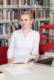 Mujer rubia feliz que trabaja en la biblioteca Fotografía de archivo libre de regalías