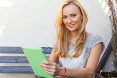 Mujer rubia feliz sensual que se sienta en banco de madera Ella está utilizando la PC móvil de la tableta Foto al aire libre Ella Fotos de archivo libres de regalías