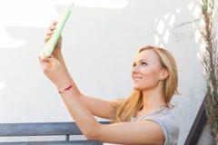 Mujer rubia feliz sensual que se sienta en banco de madera Ella está utilizando la PC móvil de la tableta Foto al aire libre Ella Fotografía de archivo libre de regalías