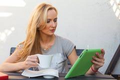 Mujer rubia feliz sensual que se sienta en banco de madera Ella está utilizando la PC móvil de la tableta Foto al aire libre Ella Imagen de archivo