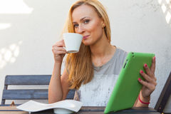 Mujer rubia feliz sensual que se sienta en banco de madera Ella está utilizando la PC móvil de la tableta Foto al aire libre Ella Foto de archivo libre de regalías