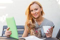 Mujer rubia feliz sensual que se sienta en banco de madera Ella está utilizando la PC móvil de la tableta Foto al aire libre Ella Fotos de archivo