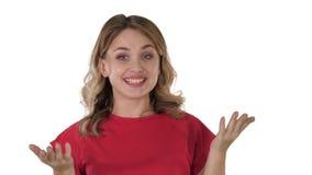Mujer rubia femenina que habla con la cámara que es muy feliz en el fondo blanco