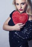 Mujer rubia hermosa atractiva con el corazón rojo. Muchacha de la belleza. Muestre el símbolo del amor. El Day.Passion de la tarje Imagen de archivo