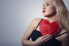 Mujer rubia hermosa atractiva con el corazón rojo. Muchacha de la belleza. Muestre el símbolo del amor. El Day.Passion de la tarje Fotos de archivo