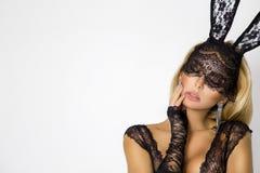 Mujer rubia hermosa, atractiva en ropa interior elegante y máscara negra del conejito de pascua del cordón fotos de archivo