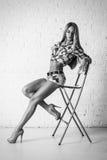 Mujer rubia hermosa atractiva joven que presenta en silla Fotos de archivo libres de regalías
