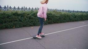 Mujer rubia hermosa bonita joven del inconformista en el windstopper rosado que tiene longboard del monopatín de la diversión que metrajes
