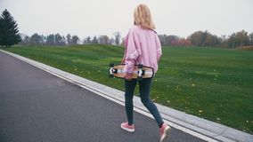Mujer rubia hermosa bonita joven del inconformista que camina abajo del camino con longboard del monopatín en la cámara lenta almacen de metraje de vídeo