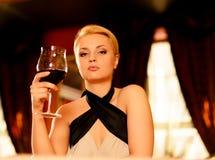 Mujer rubia hermosa con el vidrio de vino rojo Imagen de archivo