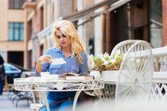 Mujer rubia hermosa con la mirada de moda que se sienta con los libros en café de la acera en día caliente del otoño Fotografía de archivo
