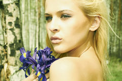 Mujer rubia hermosa con las flores azules en un bosque Imagen de archivo