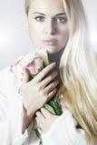 Mujer rubia hermosa con las flores de Roses.White Imágenes de archivo libres de regalías