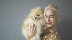 Mujer rubia hermosa con su perro de Pomerania aislado en gris metrajes