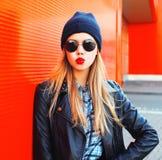 Mujer rubia hermosa del retrato de la moda que sopla los labios rojos que hacen beso del aire en un estilo del negro de la roca Fotos de archivo libres de regalías