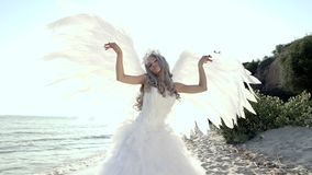 Mujer rubia hermosa delicada que presenta con costa de las alas del ángel almacen de video