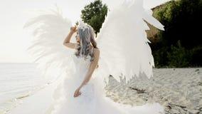 Mujer rubia hermosa delicada que presenta con costa de las alas del ángel metrajes