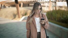 Mujer rubia hermosa en capa que camina y que mira su smartphone en otoño