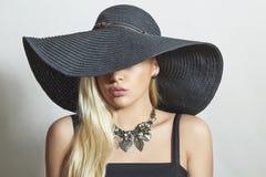 Mujer rubia hermosa en compras negras de Hat.spring Imágenes de archivo libres de regalías