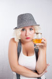 Mujer rubia hermosa en el coñac de consumición del sombrero, estilo del negocio Imagen de archivo libre de regalías