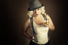 Mujer rubia hermosa en el coñac de consumición del sombrero, estilo del negocio Fotografía de archivo