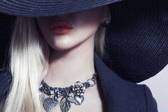 Mujer rubia hermosa en joyería negra de Hat.Spring imagen de archivo