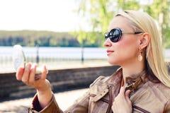 Mujer rubia hermosa en las gafas de sol loking en el pequeño espejo en la calle imagen de archivo libre de regalías