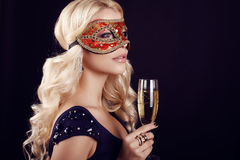 Mujer rubia hermosa en máscara del carnaval, con el vidrio de champán Foto de archivo libre de regalías