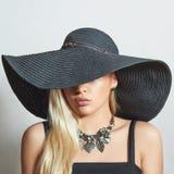 Mujer rubia hermosa en sombrero negro Primer Compras de la belleza Girl accesorios Señora en joyería foto de archivo libre de regalías