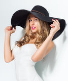 Mujer rubia hermosa en sombrero negro y el vestido de noche elegante blanco que presentan en fondo aislado Mirada de la manera st Foto de archivo libre de regalías