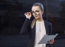 Mujer rubia hermosa en traje y vidrios con la tableta Imagen de archivo