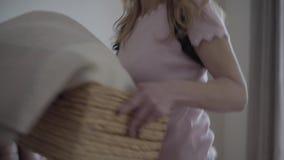Mujer rubia hermosa en un corsé ortopédico para la parte posterior que toma una caja con el paño y el paseo en casa almacen de metraje de vídeo