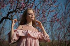 Mujer rubia hermosa en un jardín florecido imagen de archivo