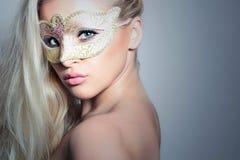Mujer rubia hermosa en un Mask.Masquerade de oro. Muchacha atractiva Fotos de archivo