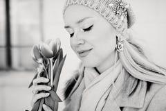 Mujer rubia hermosa en un sombrero hecho punto con las flores del tulipán Foto blanco y negro de Pekín, China fotografía de archivo
